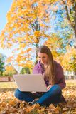 Pretty woman working outdoors in an autumn park Royalty Free Stock Images
