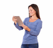 Pretty woman working on tablet pc while standing Royalty Free Stock Image