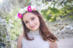 Pretty woman with wreath among apple blossom Royalty Free Stock Image
