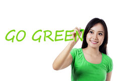 Pretty woman writes Go Green Stock Photos