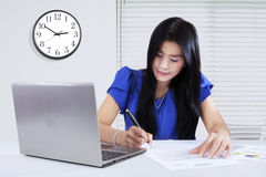 Pretty woman writing on document in office Royalty Free Stock Photography