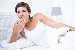 Pretty woman yawning in her bed Royalty Free Stock Photography