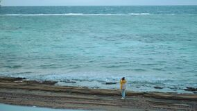 Pretty woman in yellow jacket photographs men who ride a kite surf on the sea, the waves are breaking on the shore, cold