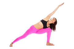 Pretty Woman in Yoga Pose - Extended Side Angle Position. Pretty woman in rextended side angle yoga pose. Isolated on white studio background Royalty Free Stock Photo
