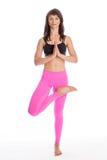 Pretty Woman in Yoga Pose - Half Lotus Tree Position. Pretty woman doing yoga in half lotus tree pose yoga. Isolated on white studio background Royalty Free Stock Image