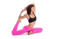 Pretty Woman in Yoga Pose - One Legged KIng Position. Pretty woman in one legged king pigeon yoga pose. Isolated on white studio background Stock Photo