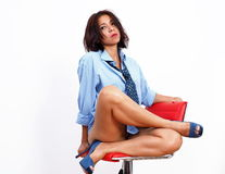 Pretty woman in yoga pose on red high chair Royalty Free Stock Photos