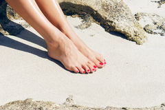 Pretty womans feet with red pedicure royalty free stock photography