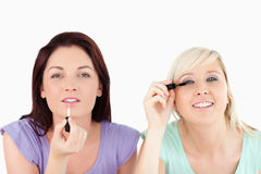 Pretty Women applying make-up Royalty Free Stock Photos