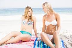 Pretty women in bikini sitting and talking on the beach Stock Image