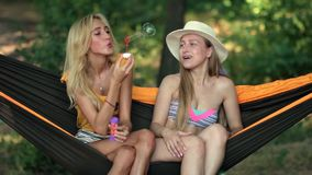 Pretty women blowing out bubbles soup on beach stock video footage