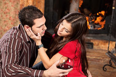 Woman caress her man near fireplace Royalty Free Stock Image