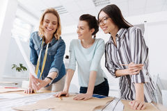 Pretty women checking out the new sketch. Have a look. Two beautiful brunette female tailors standing near the table, looking at the new outfit sketch their Royalty Free Stock Image