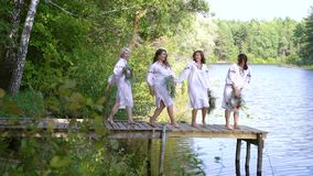 Pretty women in ethnic dresses and circlets running on pontoon bridge. Four pretty women in traditional ukraininan dresses with floral circlets running on stock footage