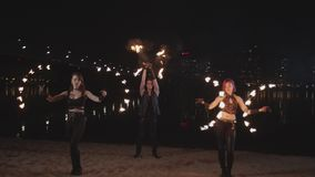 Skillful fireshow artists juggling fire by river stock video footage