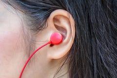 Pretty women or girl using red ear headphone to listen song. Closeup to Pretty women or girl using red ear headphone to listen song stock photo