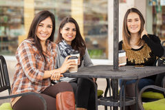 Pretty women having some coffee in a terrace. Group of three female friends hanging out and having a cup of coffee in a restaurant terrace Stock Images