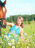 Pretty women with her horse in blossom meadow Royalty Free Stock Photography