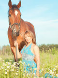 Pretty women with her horse in blossom meadow Stock Images
