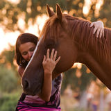 Pretty women is hugging and kissing her handsome horse. Pretty woman with her handsome horse, a senior portrait. Taken during sunset. Showing animal love Stock Photography