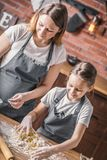 Woman with daughter cooking knead. Pretty women and little girl making knead on kitchen table together Stock Photo