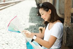 Pretty women looking a map for trip by the train at Thailand. Pretty woman looking a map for trip by the train at Thailand. Travel concept royalty free stock photo