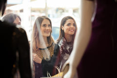 Pretty women looking at a store window display. Portrait of three beautiful female friends looking at the window display of a clothing store in a shopping mall Royalty Free Stock Photo