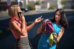 Pretty women multitask downtown. Royalty Free Stock Image
