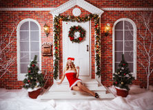 Pretty women outdoor in red clothes of santa. Seductive blonde sitting on stairs of the house Stock Images