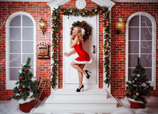 Pretty women outdoor in red clothes of santa. Sexy woman on high heels in front of the door Stock Image