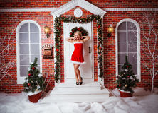 Pretty women outdoor in red clothes of santa. Very beautiful blonde wearing santa claus clothes Royalty Free Stock Photo