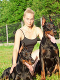 Pretty women with own dobermans Stock Photo