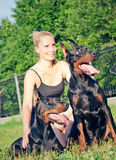 Pretty women with own dobermans Royalty Free Stock Photos