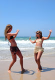 Pretty women playing on beach. Two young women taking photos of each other on a sunny beach Stock Images