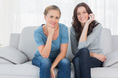 Pretty women posing while sitting on the couch Royalty Free Stock Photos