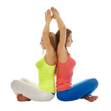 Pretty women practicing yoga in pair Royalty Free Stock Photo