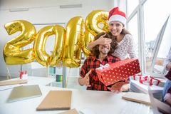 Winter holiday. Pretty women in Santa cap making surprise to her boyfriend on winter holiday Royalty Free Stock Photos