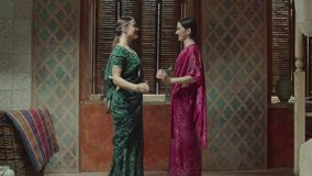 Pretty women in sari meeting and greeting each other. Charming females in colorful traditional indian sari with bracelets, bindi, tika decoration, approaching to stock footage