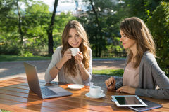 Pretty women sitting outdoors in park drinking coffee using laptop Stock Photos