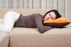 Pretty women sleeping on the couch stock photos