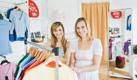 Pretty women smiling, standing in a clothes store Royalty Free Stock Photos