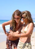 Pretty women on sunny beach. Two young women taking photos of each other on a sunny beach Royalty Free Stock Photo