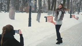 Pretty women take photo in the winter park stock video