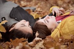 Pretty woman and teen girl are posing in autumn park. They are lying on fallen leaves. Beautiful landscape at fall season royalty free stock images