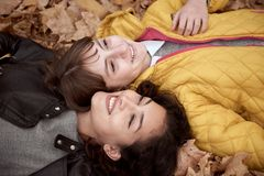 Pretty woman and teen girl are posing in autumn park. They are lying on fallen leaves. Beautiful landscape at fall season royalty free stock photography