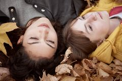 Pretty woman and teen girl are posing in autumn park. They are lying on fallen leaves. Beautiful landscape at fall season stock photo