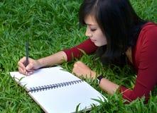 Pretty women writing book Royalty Free Stock Photos