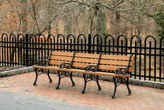 Pretty wood bench on brick patio in woodsy area. Single pretty wooden bench set on brick and stone patio in woodsy area Stock Photography