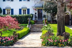 Pretty wood house with blue shutters and beautiful landscaping and a bright floral decorative flag by door - with Japanese Maple a. Nd pink tulips royalty free stock photo