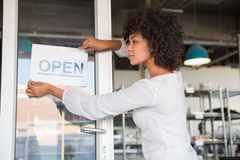 Pretty worker putting up a open sign Stock Images
